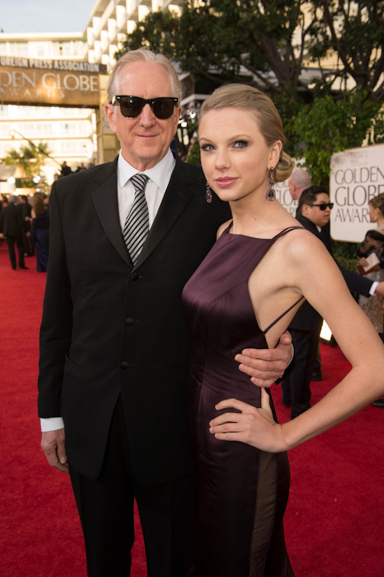 Golden Globes 2013: Producer T-Bone Burnett and singer Taylor Swift in a dark magenta colored ballgown by Donna Karan.