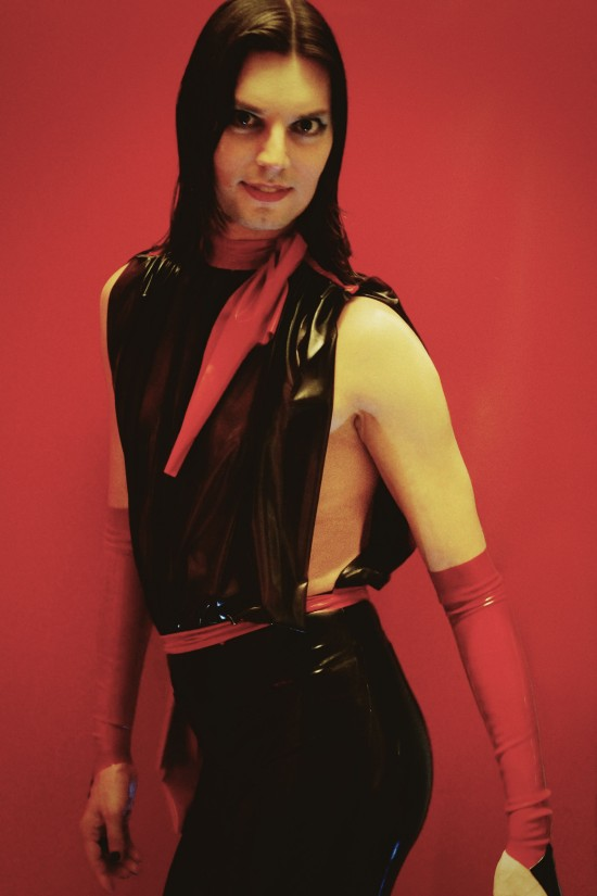 A black and red latex jumpsuit with a draped top and two red bows. Designed by Rubberik.